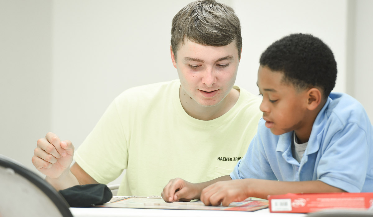 Catholic University Student tutoring child