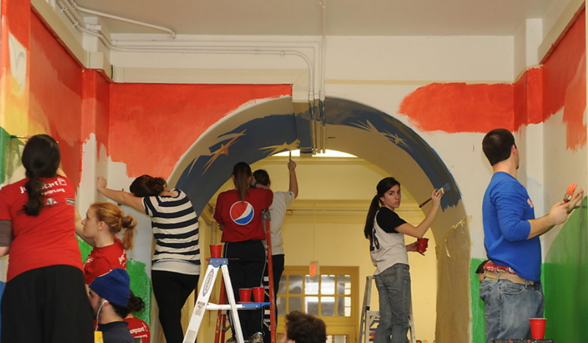 Catholic University students painting a hallway